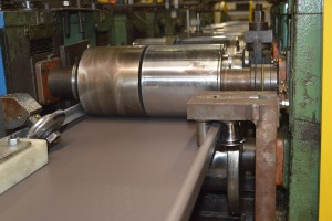Precisely and exactly formed standing seam panels exiting the roll former and going into the cut-to-length operation.